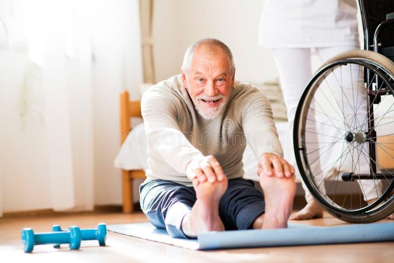 Gesundheitsbesucher und älterer Mann während des Hausbesuchs lizenzfreie stockbilder