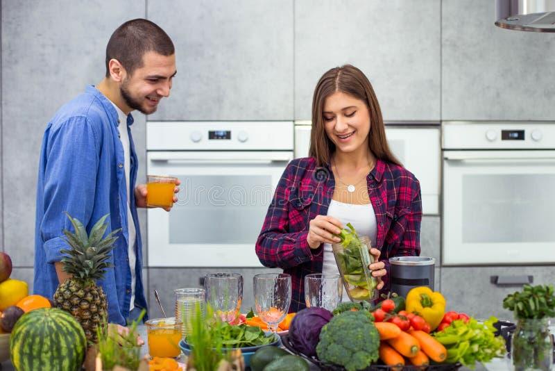 Gesundheitsfr?hst?ck f?r ein junges Paar den morgens, Mann, der Orangensaft und Dame zubereitet den Smoothie in a trinkt lizenzfreies stockfoto