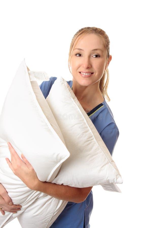 Gesundheitspflegearbeitskraft, die geduldige Kissen trägt lizenzfreie stockbilder