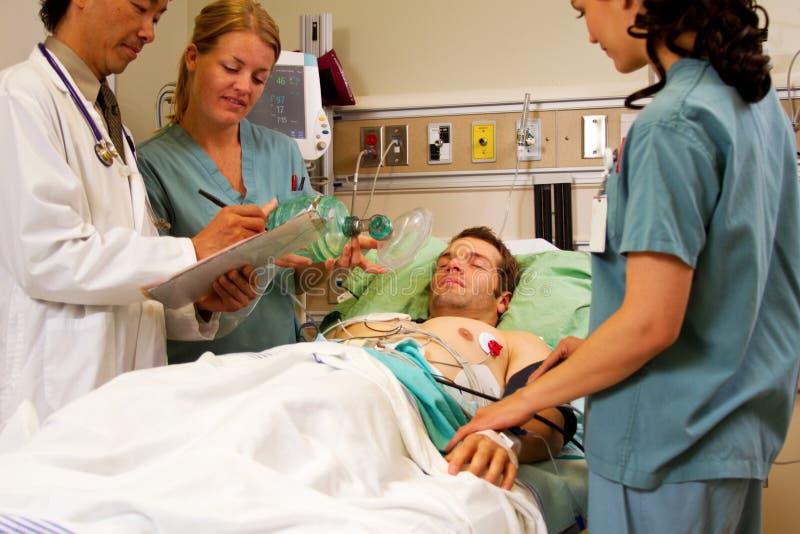 Gesundheitsteam, das Patienten im Notfall behandelt lizenzfreie stockfotografie