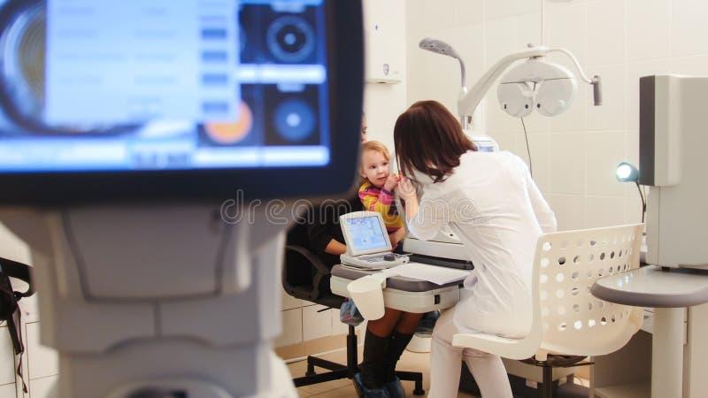 Gesundheitswesen - Optometriker in der Augenheilkundeklinik kleines Kind-` s Vision überprüfend lizenzfreie stockbilder