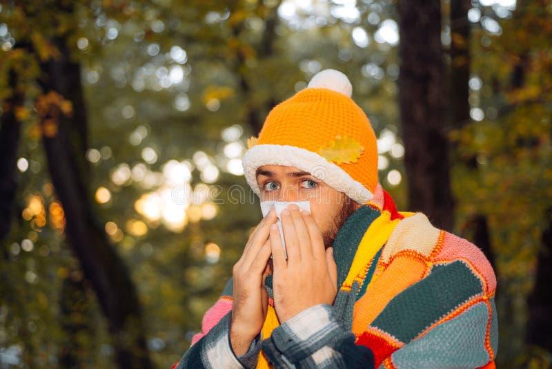 Gesundheitswesen- und Medizinkonzept - kranker Mann mit Papiergewebe im Herbstpark Reifer Mann in der Jacke, die unter Kälte leid lizenzfreie stockbilder