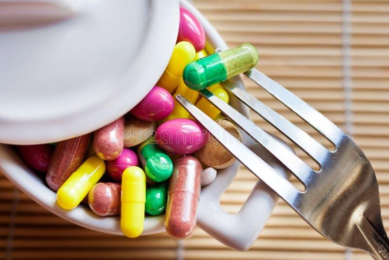 Gesundheitswesen und Wellness - nähren Sie Pillen und Lösengewicht - verschiedene Tabletten in einem Topf mit Gabeln lizenzfreie stockbilder