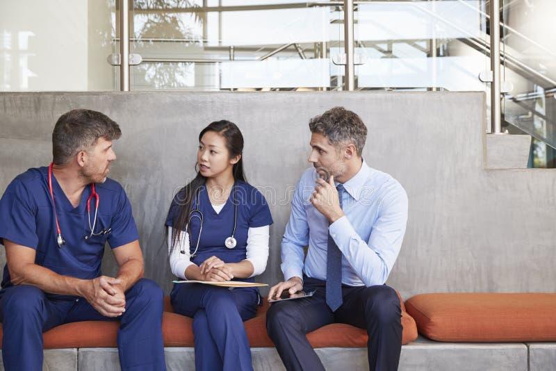 Gesundheitswesenarbeitskräfte sprechen das Sitzen auf einer Bank im Krankenhaus stockfotos