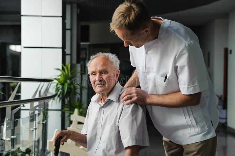 Gesundheitswesenarbeitskraft und älterer Patient stockfotografie