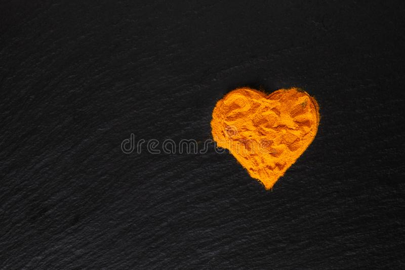 Gesundheitswesenkonzept Gelbwurz-Gewürzpulver in der Herzform im schwarzen Hintergrund stockfotografie