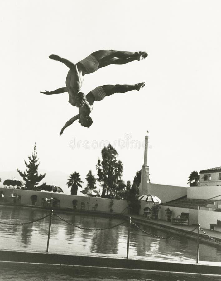 Gesynchroniseerde duikers in mid-air royalty-vrije stock afbeelding