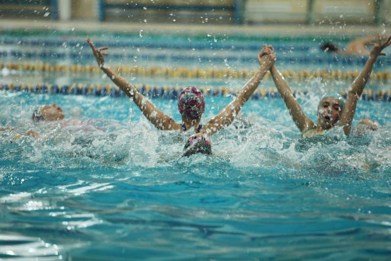 Gesynchroniseerde zwemmende overwinningsplonsen van succes stock afbeelding