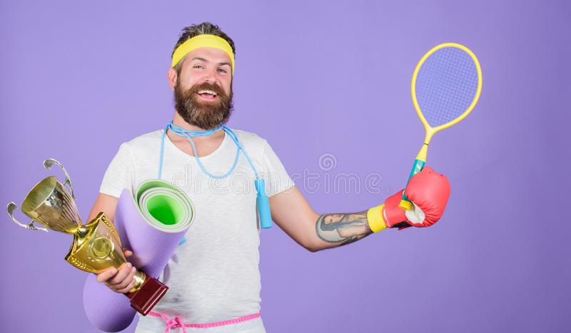 Get body ready for summer. Choose sport you like. Man bearded athlete hold sport equipment jump rope fitness mat boxing. Glove expander racket and golden goblet stock photo