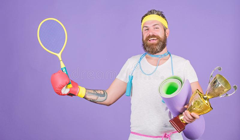 Get body ready for summer. Choose sport you like. Man bearded athlete hold sport equipment jump rope fitness mat boxing. Glove expander racket and golden goblet stock image