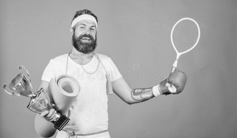 Get body ready for summer. Choose sport you like. Man bearded athlete hold sport equipment jump rope fitness mat boxing. Glove expander racket and golden goblet royalty free stock photo