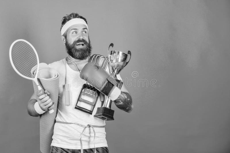 Get body ready for summer. Man bearded athlete hold sport equipment jump rope fitness mat boxing glove expander racket. And golden goblet. Choose sport you like stock photography