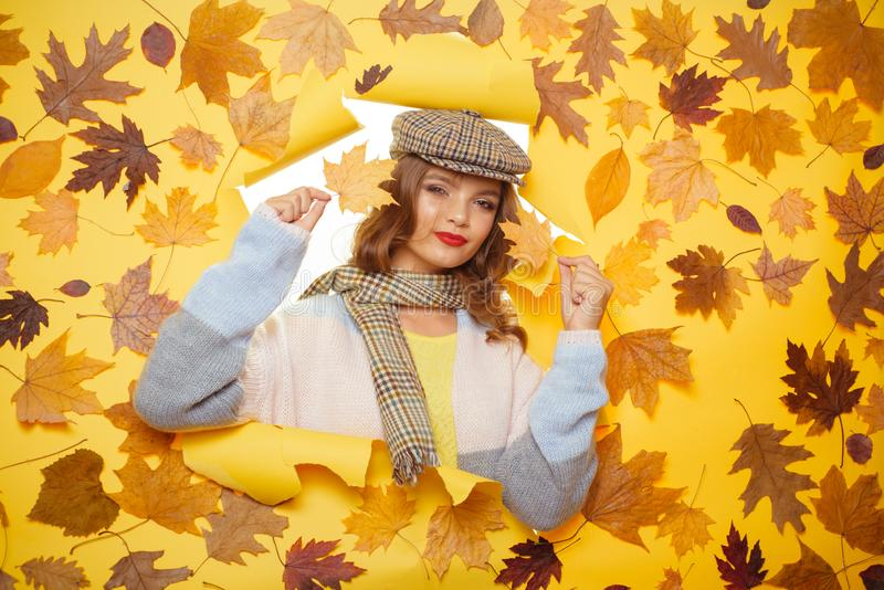 Get comfy wearing this fantastic scarf. Casual fashion trends for fall. Fashion girl look through torn paper with autumn stock image