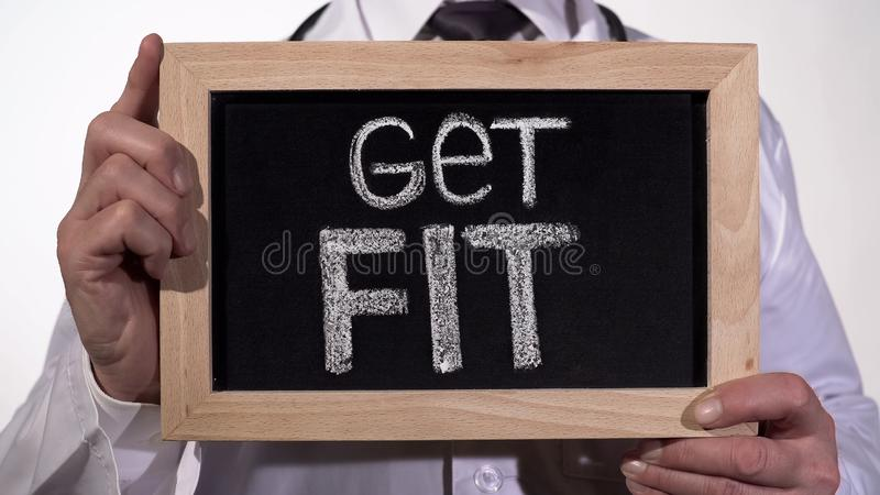 Get fit written on blackboard in doctor hands, active healthy life promotion stock photography