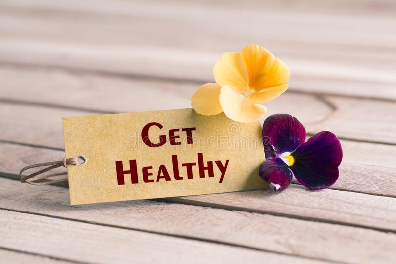 Get healthy tag. Tag banner get healthy and violet flower on wooden desk stock images