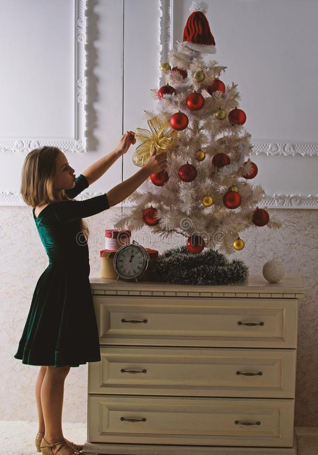 Get incredibly excited about christmas. Kid girl near christmas tree waiting midnight clock. Last preparations. Child royalty free stock image
