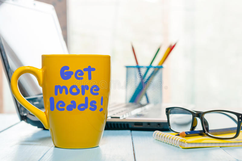 Get more leads motivation phrase on yellow cup of morning coffee or tea at business office workplace backgound. With stock photo