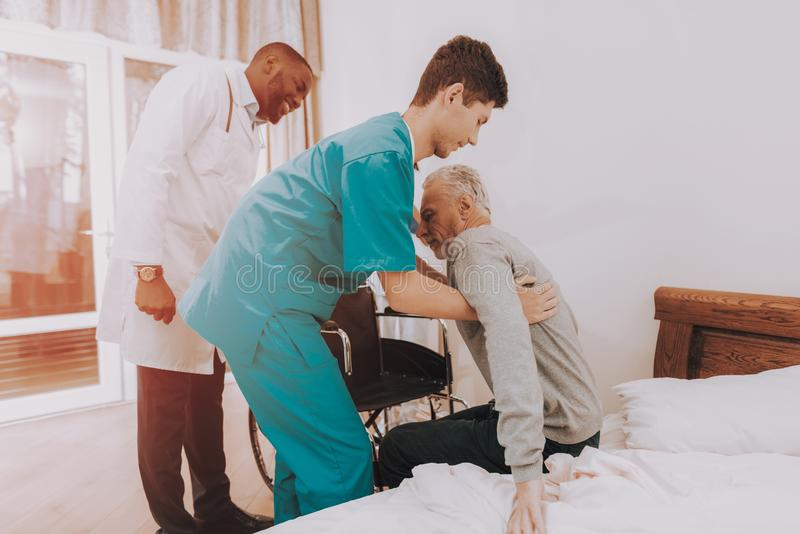 Get Out of Bed. Nurse Helps. Elderly Man. Patient. stock image