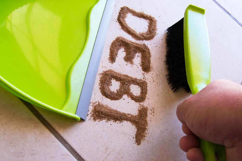 Get out of Debt Concept. With debt written in dirt on a floor and a person is about to sweep the debt dirt in a dust pan using a small hand broom stock images