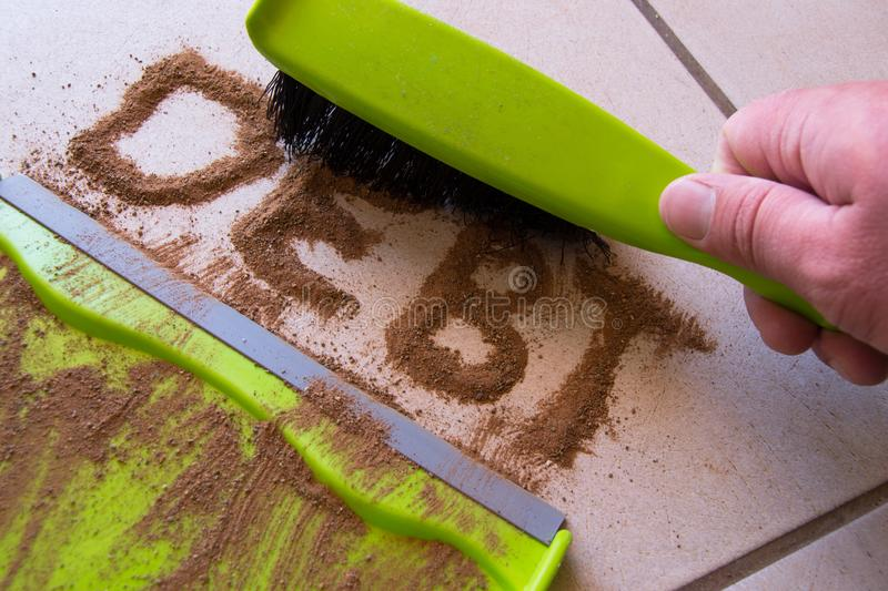 Get out of Debt. With debt written in dirt on a floor and a person is about to sweep the debt dirt in a dust pan using a small hand broom royalty free stock image