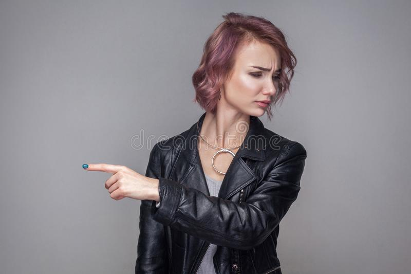 Get out from here. Portrait of dissatisfied woman with short hair and makeup in casual style black leather jacket standing and royalty free stock photos