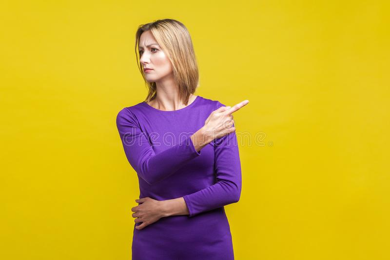 Get out! Portrait of angry bossy woman looking aside and pointing finger another way.  on yellow royalty free stock images