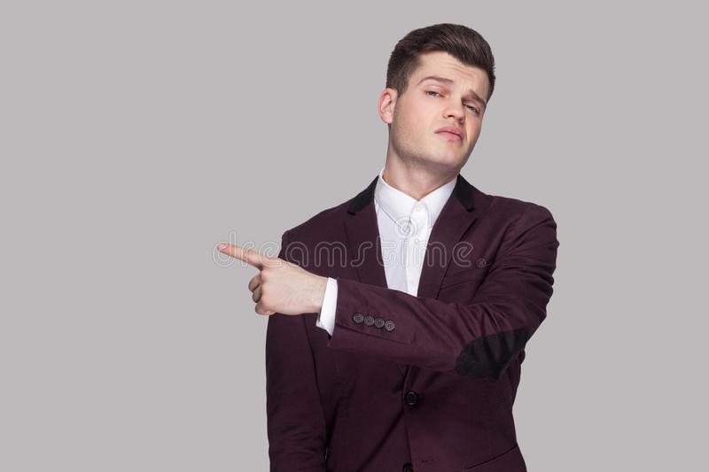Get out. Portrait of serious handsome young man in violet suit a stock photography