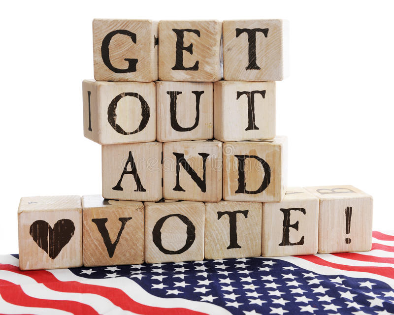 Get Out and Vote!. Rustic alphabet blocks arranged to say, Get out and Vote! sitting on a bed of stars and stripes. On a white background royalty free stock image