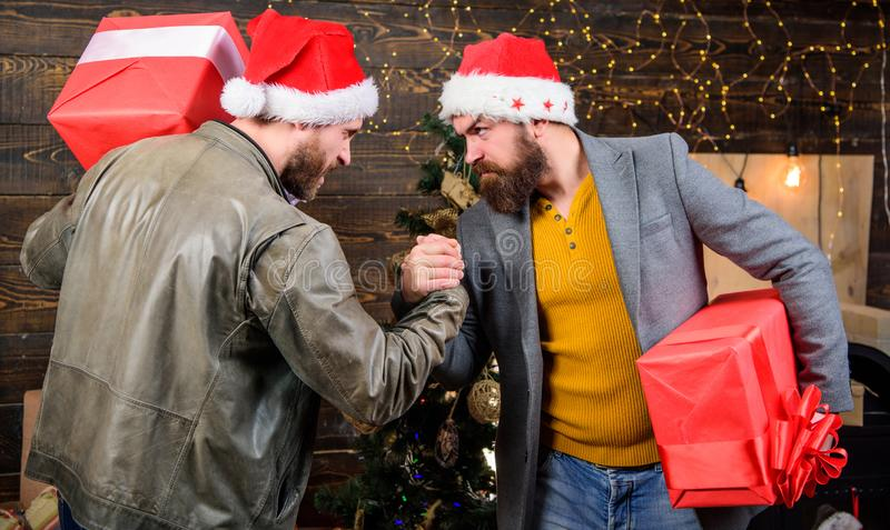 Get ready for christmas. Men wear santa hat hold gift boxes. Bearded men carry present boxes. Brutal hipster guys. Celebrate christmas with gifts. Delivery stock images