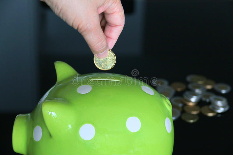 Get rich. A hand is putting a coin into a big saving jar. On side, there are a lot of coins. This is a way to get rich. It signifies saving, getting rich and royalty free stock images
