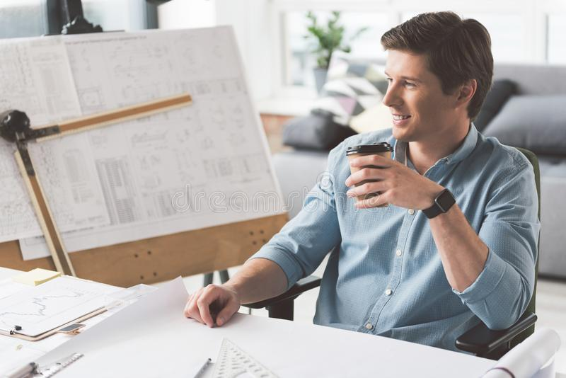 Cheerful attractive engineer is enjoying espresso royalty free stock photo