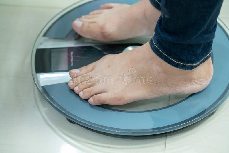 Get weighing. Women standing on weighing machine to measure her weight royalty free stock photo