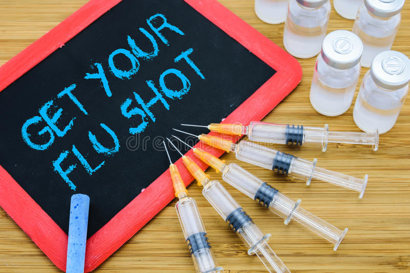 Get Your Flu shot written on chalkboard with vaccine in syringes. Reminder to Get Your Flu shot written on chalkboard with vaccine in syringes and vials stock photos