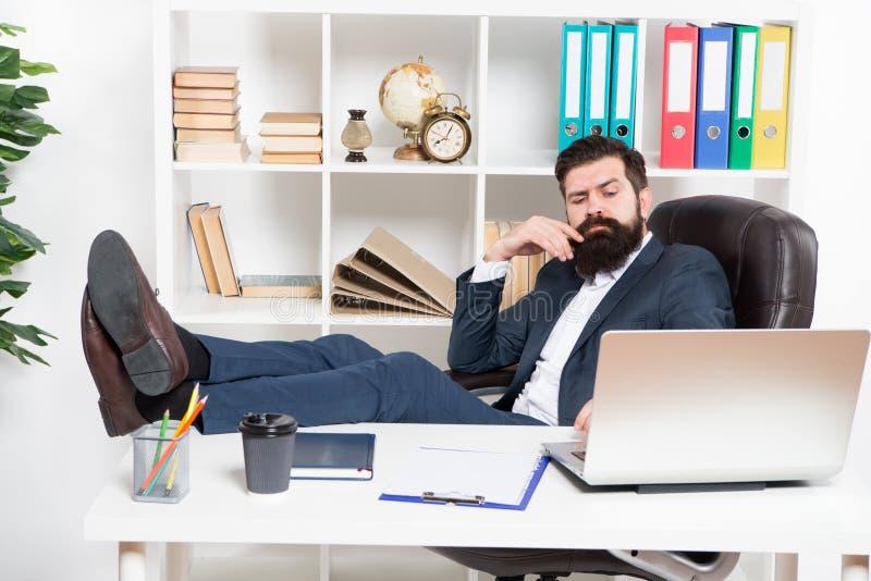 Getan genug für heutigen Tag Sitzen bärtiger Hippie-Chef des Mannes im Ledersesselbüroinnenraum Chef am Arbeitsplatz Manager stockfotos