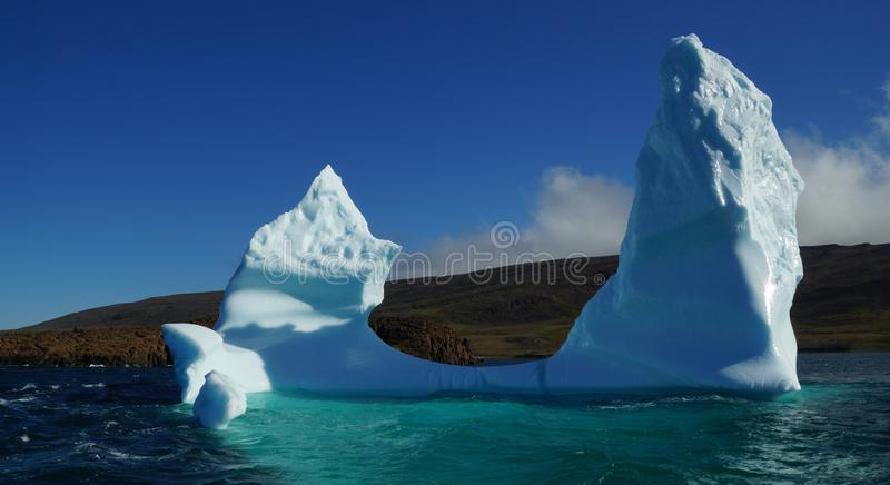 Getande ijsberg die met een mooie blauwe bezinning in het water drijft stock afbeeldingen