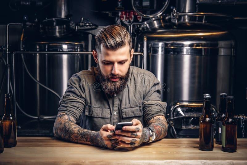 Getatoeeerd hipster mannetje met modieuze baard en haar die smartphone gebruiken terwijl het zitten bij barteller in de indiebrou stock afbeeldingen