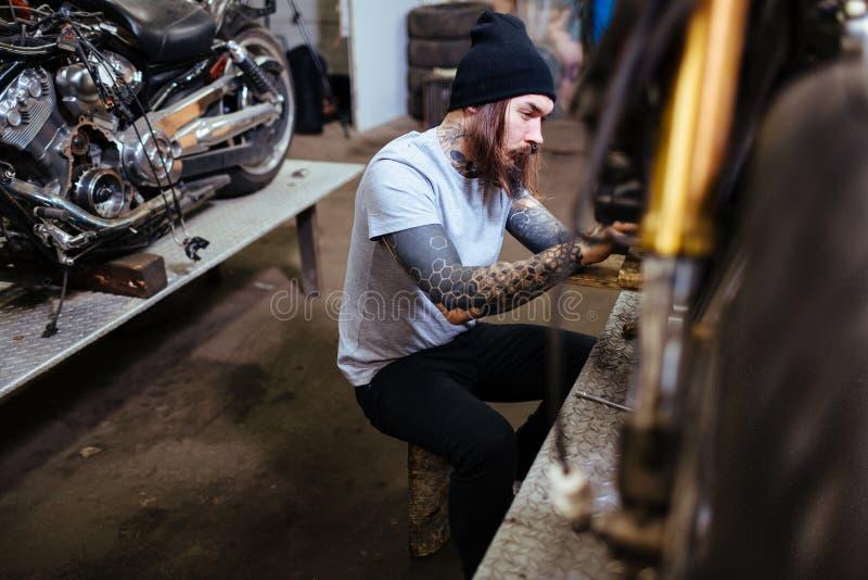 Getatoeeerde Fiets Mechanisch Assembling Motorcycle in Garage stock afbeeldingen