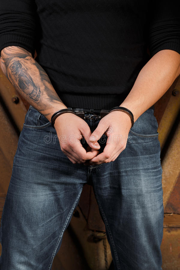 Getatoeeerde handen van de handboeien om:doen misdadig stock foto