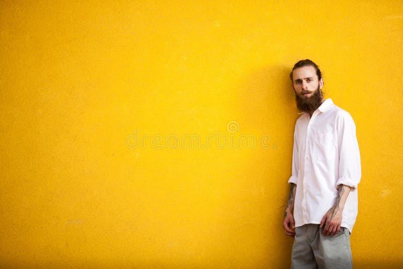 Getatoeeerde manier gebaarde hipster op gele muur royalty-vrije stock foto's