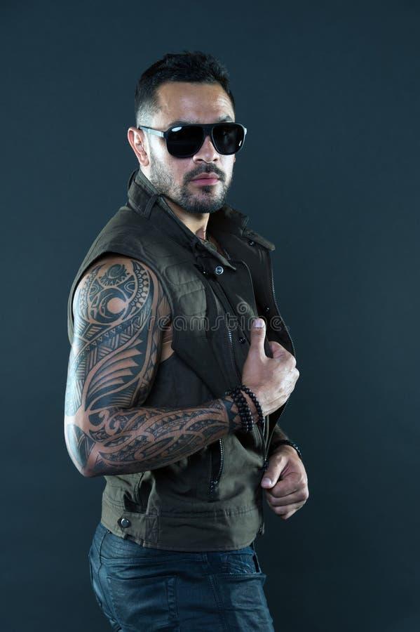 Getatoeeerde mens met bicepsen en triceps Tatoegeringsmodel met baard op ongeschoren gezicht Gebaarde mens met tatoegering op ste stock foto