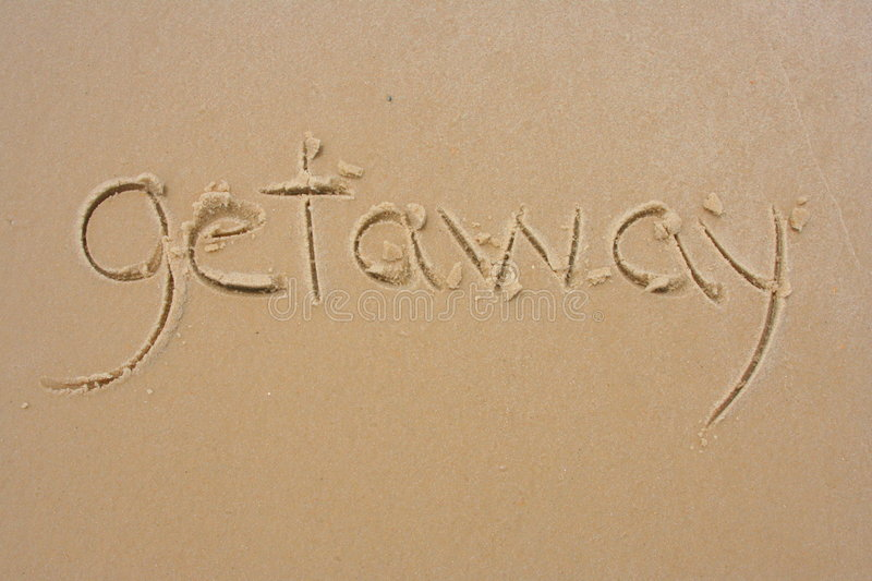 Getaway in the sand. Getaway written in the sand stock images