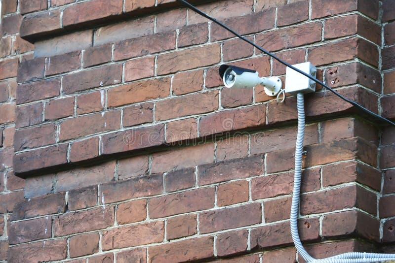 Getelegrafeerde toezichtcamera opgezet op een bakstenen muur De witte camera van de draad anti-diefstal veiligheid opgezet op een stock fotografie