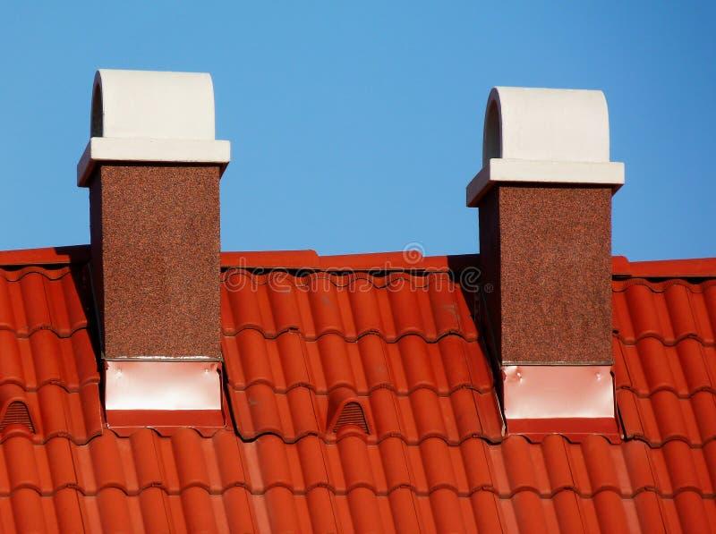 Getextureerde schoorstenen afgewerkt door stucco met witte keramische houten steen boven geslepen klei dakpannen royalty-vrije stock afbeelding