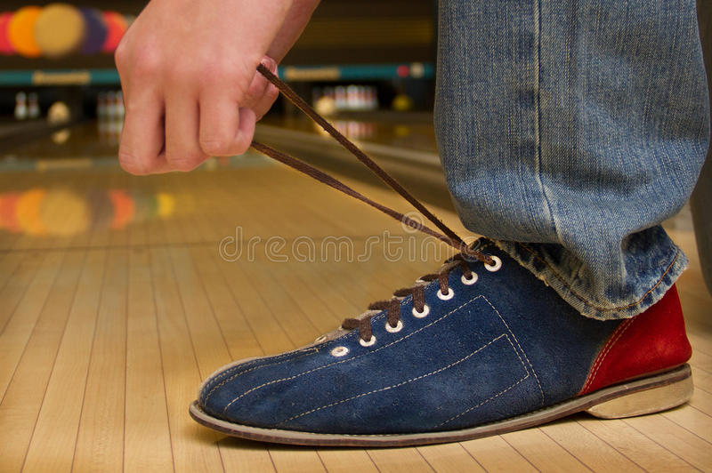 Geting ready for bowling!. Hands tying lais of shoe in bowling alley stock photo