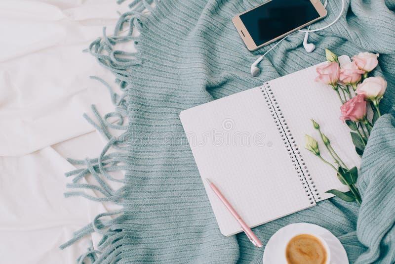 Getonte Ebene legen Tablette, Telefon, Tasse Kaffee und Blumen auf weiße Decke mit Türkisplaid stockfoto