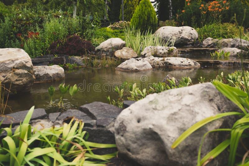 Getontes Bild des formalen Gartens mit großen Felsen und schnellem Strom lizenzfreies stockfoto