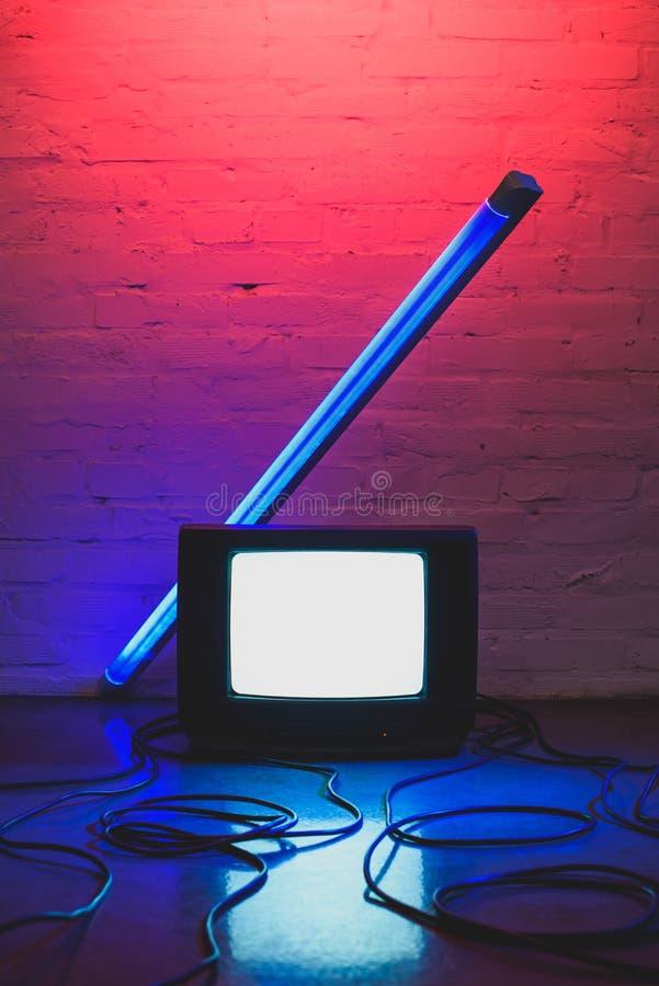 getontes Bild des vereinbarten Retro- Fernsehers, der Kabel und der Lampe mit Ziegelstein lizenzfreie stockfotos