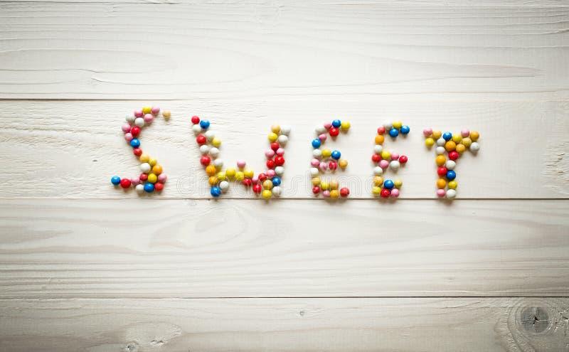 Getontes Bild von Wort Bonbon gemacht von den bunten Süßigkeiten auf weißem Holz lizenzfreie stockfotos