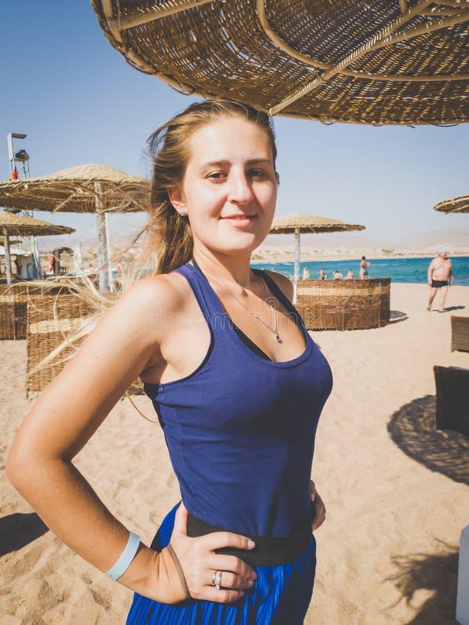Getontes Nahaufnahmeporträt der schönen lächelnden jungen Frau mit dem langen Haar auf dem Strand am windigen Tag lizenzfreies stockfoto