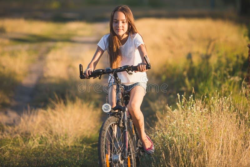 Getontes Porträt des schönen Jugendlichereitfahrrades auf Landschaftsstraße bei Sonnenuntergang lizenzfreies stockfoto